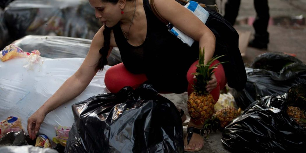 Mujer buscando en la basura
