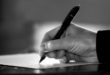 close-up of a man's hand signing document/contract or writing (black and white).