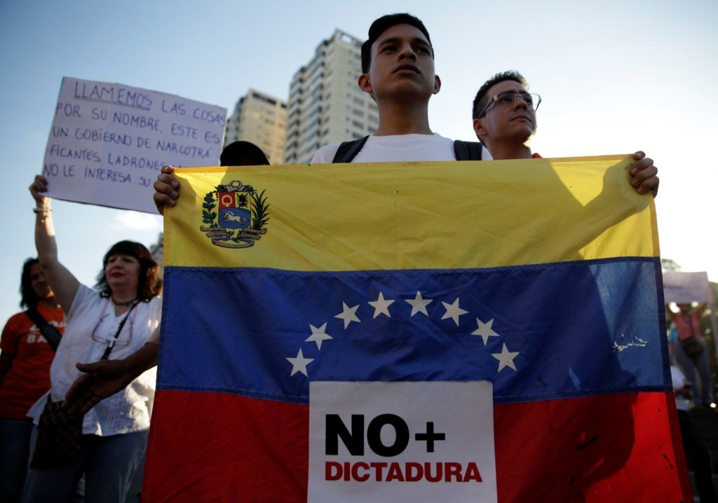 "An opposition supporter holds a Venezuelan flag with a sign that reads ""No more dictatorship"" during a protest against Venezuelan President Nicolas Maduro's government, in Caracas, Venezuela March 30, 2017. REUTERS/Marco Bello"