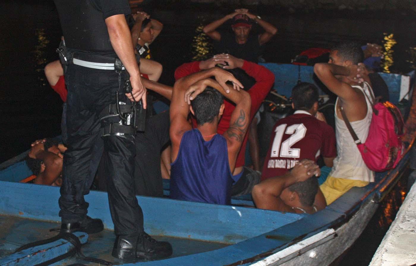 En esta fotografía del sábado 6 de agosto de 2016, autoridades detienen una embarcación en la que viajaban 20 migrantes venezolanos y uno colombiano en la subestación de la guardia costera en Parera, Curazao. La policía decomisó contrabando como cigarrillos y municiones y detuvo a todas las personas que viajaban a bordo porque presuntamente intentaban ingresar ilegalmente en Curazao. El portavoz de la Guardia Costera, Roderick Gouverneur, dijo que todos los migrantes estaban detenidos el lunes. (Foto de Roderick N. Gouverneur/Guardia Costera Caribeña Holandesa)